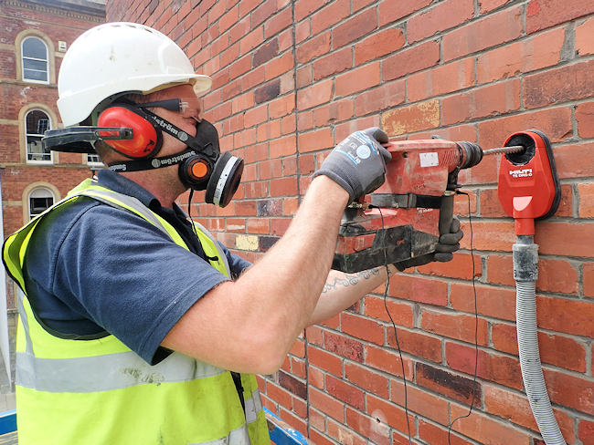 Brick-Tie employee drilling with dust suppression, eye protection and face fit tested dust mask and